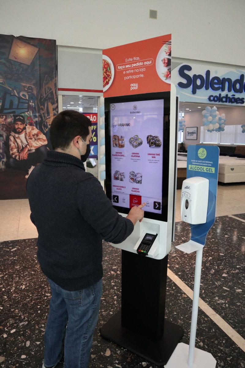 Cliente usando o Totem Multi Loja de Operações de Alimentação. Tudo integrado e fácil!